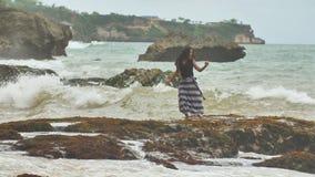 Ein junges indonesisches Mädchen ist zu den großen Wellen auf dem felsigen Ufer der Insel von Bali froh stock video