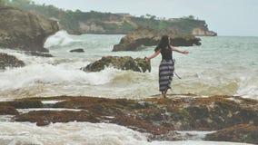 Ein junges indonesisches Mädchen ist zu den großen Wellen auf dem felsigen Ufer der Insel von Bali froh stock video footage