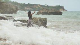 Ein junges indonesisches Mädchen ist zu den großen Wellen auf dem felsigen Ufer der Insel von Bali froh stock footage