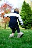 Ein junges Kind, das Schuhe seines Vaters trägt Lizenzfreie Stockfotos