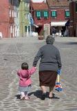 Ein junges Kind und ihre Großmutter gehen entlang die Straßen von Bura Lizenzfreies Stockbild