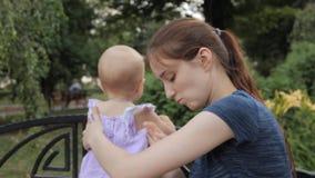 Ein junges Kindermädchen, das den Smartphoneschirm betrachtet, ihr Haar verstaut, beiseite den Smartphone setzt und ein Baby befö stock video footage