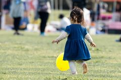 Ein junges kleines Mädchen, das einen gelben Ballon und mit ihm im Park spielen jagt lizenzfreies stockbild