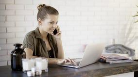 Ein junges lächelndes Mädchen hat einen Anruf, der mit einem Laptop wotking ist Lizenzfreies Stockbild