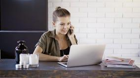 Ein junges lächelndes Mädchen hat einen Anruf, der mit einem Laptop wotking ist Stockfotos