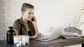 Ein junges lächelndes Mädchen hat einen Anruf, der mit einem Laptop wotking ist Lizenzfreies Stockfoto