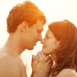 Ein junges liebevolles Paar, das auf dem Strand an den Sonnen umarmt und küsst lizenzfreies stockfoto