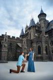 Ein junges liebevolles Paar, das nahe vom Schloss geht Hochzeitsreise zu den Flitterwochen Stockfotografie