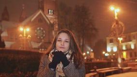 Ein junges Mädchen auf dem Hintergrund der Abendstadt wärmt kalte Hände auf Im Licht des Stadtlichtschneiens stock footage