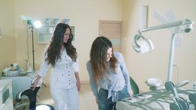 Ein junges Mädchen auf eine Aufnahme mit einem Zahnarzt langsam, schießend, kam in das Büro, hingesetzt in einem zahnmedizinische stock video