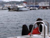 Ein junges Mädchen auf einer Yacht blickt heraus in Richtung des Hafens Stockfotografie