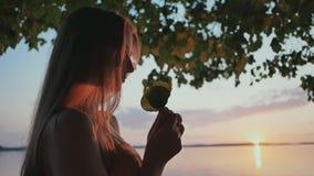 Ein junges Mädchen berührt das Blumenblatt bei Sonnenuntergang nahe dem See stock video footage