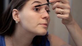Ein junges Mädchen bereitet sich für ein romantisches Abendessen vor und tut Make-up, zeichnet Augenwimperntusche stock footage