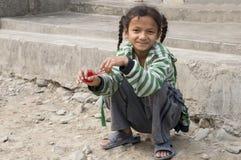 Ein junges Mädchen, das auf der Straße sitzt stockfoto