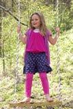 Ein junges Mädchen, das auf einem Schwingen steht Stockbild