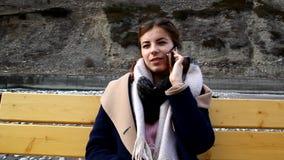 Ein junges Mädchen, das auf einer Bank sitzt und am Telefon spricht stock video footage