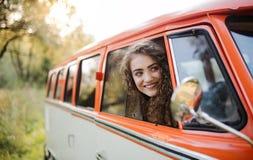 Ein junges Mädchen, das aus einem Auto auf einem roadtrip heraus durch Landschaft schaut stockbild