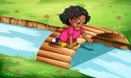 Ein junges Mädchen, das an der Holzbrücke spielt Lizenzfreies Stockfoto