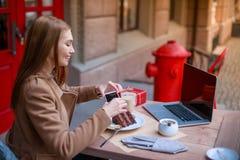 Ein junges Mädchen, das in einem Café mit einem Laptop sitzt und fotografiert ihren Nachtisch an einem Handy lizenzfreie stockfotografie