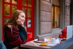 Ein junges Mädchen, das in einem Café sitzt, einen Becher hält und mit einem offenen Laptop lächelt draußen Im Herbst Die Küken w stockfoto