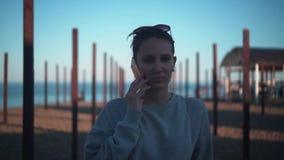 Ein junges Mädchen, das an einem Handy auf dem See im Hintergrund der Stadt in den Strahlen der Sonne bei Sonnenuntergang spricht stock footage