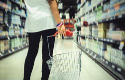 Ein junges Mädchen, das einen Einkaufskorb A hält, verwischte Hintergrund Lizenzfreie Stockfotos