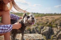 Ein junges Mädchen, das ihren Hund auf einem unscharfen natürlichen Hintergrund streichelt Ein kleiner Hund in den weiblichen Hän Lizenzfreies Stockfoto