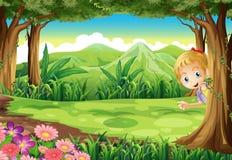 Ein junges Mädchen, das Verstecken am Wald spielt stock abbildung