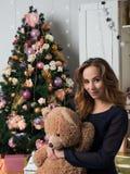 Ein junges Mädchen, das vor einem Weihnachtsbaum und Umarmungen ein Spielzeugbär sitzt Der Geist von Weihnachten und eine Richtun stockfoto