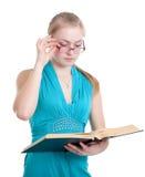 Ein junges Mädchen in den Gläsern mit einem Buch Stockfotos