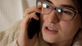 Ein junges Mädchen in den Gläsern spricht am Telefon stock footage