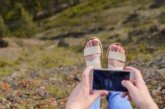Ein junges Mädchen in der blauen Kleidung, tragende Sonnenbrille, macht Fotos im Sommer Lizenzfreie Stockbilder