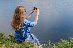 Ein junges Mädchen in der blauen Kleidung, tragende Sonnenbrille, macht Fotos im Sommer auf der Straße Lizenzfreies Stockfoto