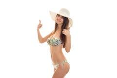 Ein junges Mädchen in einem Badeanzug und in einem Hut wert sich drehen seitlich und Shows die Klasse Stockfoto