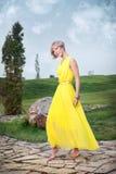 Ein junges Mädchen in einem gelben Kleid stockfotos