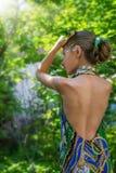 Ein junges Mädchen in einem Kleid mit Akt unterstützt Wert im Haar des Laubs im Wald, das mit Laub verziert wird Lizenzfreies Stockfoto