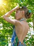 Ein junges Mädchen in einem Kleid mit Akt unterstützt Wert im Haar des Laubs im Wald, das mit Laub verziert wird Lizenzfreie Stockbilder