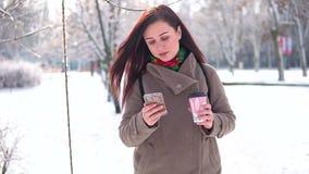 Ein junges Mädchen, in einem Mantel, schlendert durch den Winterpark, schreibt eine Mitteilung und trinkt Kaffee stock video