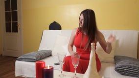 Ein junges Mädchen in einem roten Kleid bereitete Kerzen, Gläser für ein romantisches Abendessen und Wartezeiten für ihren Eheman stock video footage