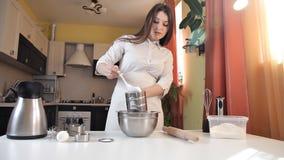 Ein junges Mädchen in einem Schutzblech in der Küche bereitet Produkte für den Kuchen vor Kühlschrank, Eier, Teig stock video