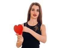 Ein junges Mädchen in einem schwarzen Kleid schaut nach vorn und eine Herz geformte Karte halten Lizenzfreies Stockbild