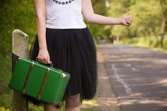 Ein junges Mädchen in einem weißen Trägershirt und schwarzes flaumiges Rockballettröckchen umsäumen das Fangen eines Autos auf de lizenzfreies stockfoto