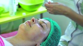 Ein junges Mädchen an einer Aufnahme mit einem Cosmetologist The-Kosmetiker reinigt das Gesicht und macht Schale stock footage