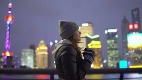 Ein junges Mädchen in einer schwarzen Jacke und in den Hutwegen um das schöne Shanghai mit Kaffee in ihren Händen stock video