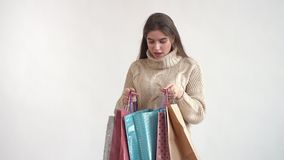 Ein junges Mädchen in einer warmen Strickjacke mit beiden Händen öffnet die Pakete und öffnet ihren Mund überrascht und betrachte stock video