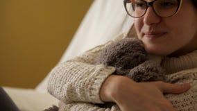 Ein junges Mädchen in einer weißen Strickjacke und in tragenden Gläsern wird mit einem weichen Spielzeug gespielt kindheit Spielw stock footage