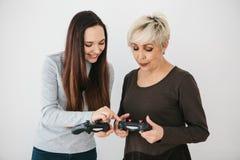 Ein junges Mädchen erklärt einer älteren Frau, wie man den Steuerknüppel für Videospiele benutzt Gemeinsamer Zeitvertreib Moderne stockbild