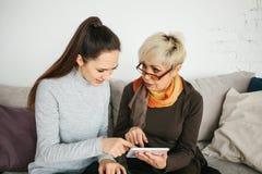 Ein junges Mädchen erklärt einer älteren Frau, wie man eine Tablette benutzt oder zeigt irgendeine Anwendung oder bringt Ihnen be stockfotos