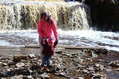 Ein junges Mädchen geht mit ihrem Kind am Wasserfall lizenzfreie stockfotografie