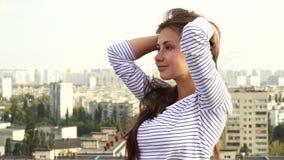 Ein junges Mädchen genießt das Wetter bei der Stellung auf dem Dach stockbild